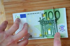 cutting one hundred euro banknote - stock photo