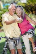 senior couple bicycles taking digital camera picture - stock photo