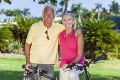 Happy senior couple on bicycles in park Stock Photos