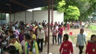Stock Video Footage of Textile Garment Factory: Crowd of female workers passes outdoor lunch hall