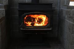 Fire through glass in a wood stove Stock Photos