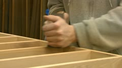 A woodworker hand-planes a wood project Stock Footage