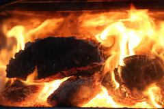 Fire through glass in a wood stove - stock photo