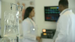 Rack focus from IV bag to doctors Stock Footage