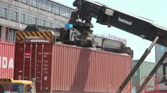 SHIPPING PORT: Great shot of loader lifting and moving shipping container - stock footage