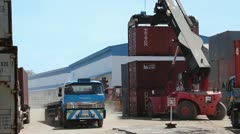 SHIPPING PORT: Great shot of container loader with truck passing Stock Footage