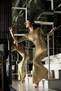 Stock Photo of pretty woman in beautiful gold dress on stairs