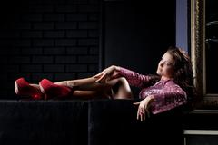 Stock Photo of young beauty brunette woman relax on black sofa
