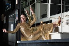 Stock Photo of amazing young woman in gold dress smile on stairs