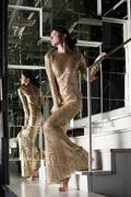 young woman in gold dress on stairs - stock photo