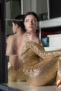 Stock Photo of beauty woman portrait in gold dress on stairs