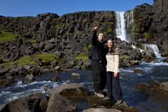 Romantic couple woman and man by a waterfall Stock Photos