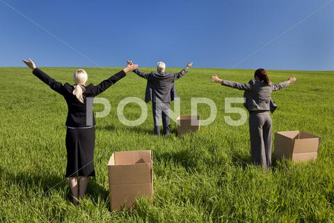 Stock photo of business team men and women in green field