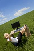 woman relaxing in a green field office - stock photo