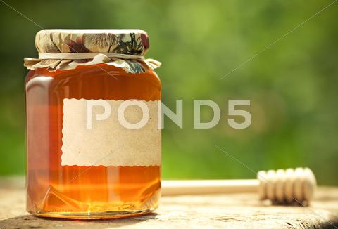 Stock photo of flowery honey in glass jar