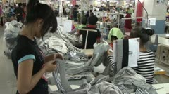 Textile Garment Factory: Medium shot many workers check pile of grey fabrics Stock Footage