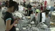 Stock Video Footage of Textile Garment Factory: Medium shot many workers check pile of grey fabrics