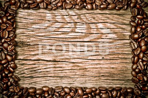 Stock photo of coffee beans on wood texture