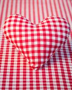 Red heart on gingham tablecloth Stock Photos
