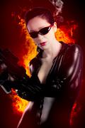 Sexy brunette woman in latex jumpsuit with heavy gun over fire background Stock Illustration