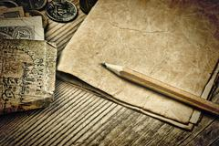Old notes and coins and pencil on a wooden table Stock Photos