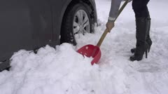 SLOW MOTION: Woman shoveling car out of snow. Stock Footage