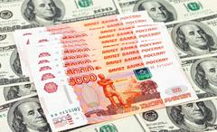 Russian roubles bills laying over dollars background Stock Photos