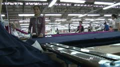 Textile Garment Factory: Garment workers slide saw back and forth - stock footage