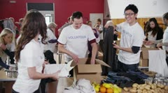 Charity volunteers sorting through donated goods Stock Footage