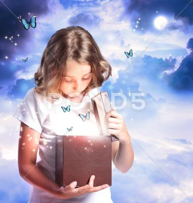 Stock photo of girl opening a box with blue butterflies