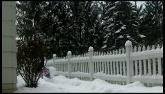 Snow Shoveling along sidewalk with picket fence Stock Footage