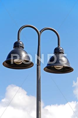 Stock photo of a double hooded street light with blue sky background