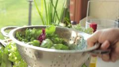 Washed fresh salad falls into the metal colander , slow motion HD Stock Footage