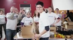 "Charity worker holds up a ""Please Give"" sign as his fellow workers applaud Stock Footage"