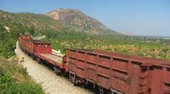 A Freight goods train is passing by a rural station in India. Stock Footage