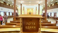 People walk in synagogue with jewish wooden box for charity Stock Footage