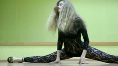 Girl does splits on floor in dance near green wall with mirror Stock Footage