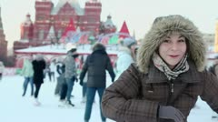 Young girl in winter coats with hoods skates on Red square Stock Footage