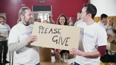 "2 Charity workers hold up a ""Please Give"" sign as their fellow workers applaud - stock footage"