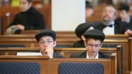 Jewish boys and other curchgoers sit on bench in synagogue Stock Footage
