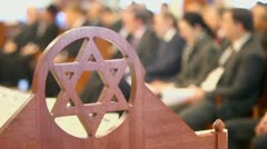 Many sit in synagogue behind wooden merkaba symbol at memorial Stock Footage