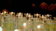 Man in suit ignites candle by match at memorial in dark Stock Footage