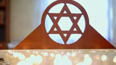 Many candles burn near wooden merkaba symbol at memorial Stock Footage