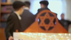 Jewish boys near funeral candles and wooden merkaba in synagogue Stock Footage