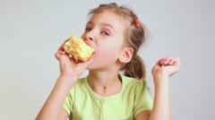 Little girl in a green blouse eats large red juicy apple Stock Footage
