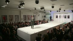 Model with coat walks runway in fashion house of Slava Zaitsev Stock Footage