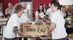 "2 Charity workers hold up a ""Thank you"" sign as their fellow workers applaud Stock Footage"