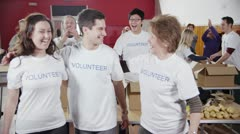 3 Charity workers embrace and smile to camera as their fellow workers applaud - stock footage
