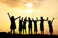 Group of happy children standing on meadow at summer sunset Stock Photos