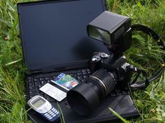 Digital camera and notebook. Stock Photos